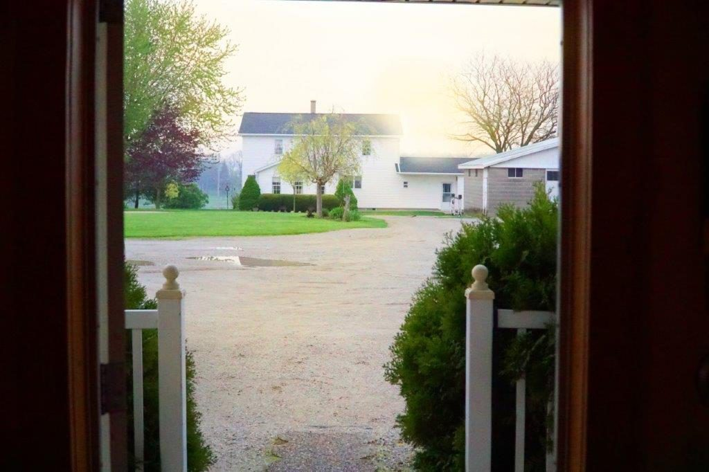 The view from the front door of a woodshop: the rising sun and the home of the woodshop owners.