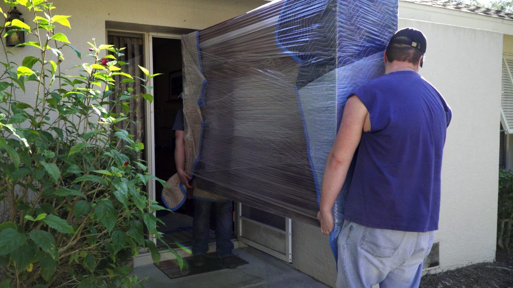 Two movers lift a hutch through a pre-measured doorway.