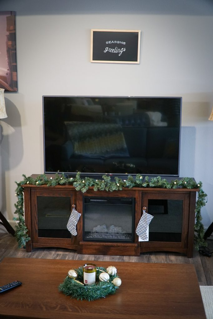 Flint Electric Fireplace with garland, stockings, and season's greeting chalkboard
