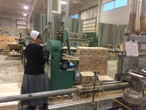 A woodworker putting chair legs into the machine.