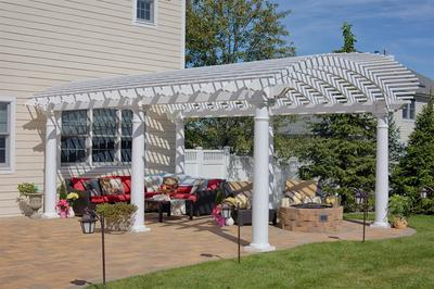 Amish Arcadian Vinyl Pergola on the side of a house.
