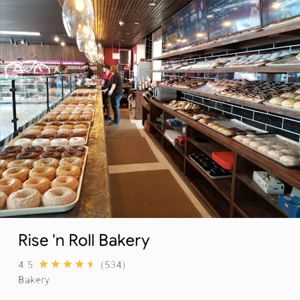 Photo of donuts and employees from the end of and behind the counter at Rise 'n Roll